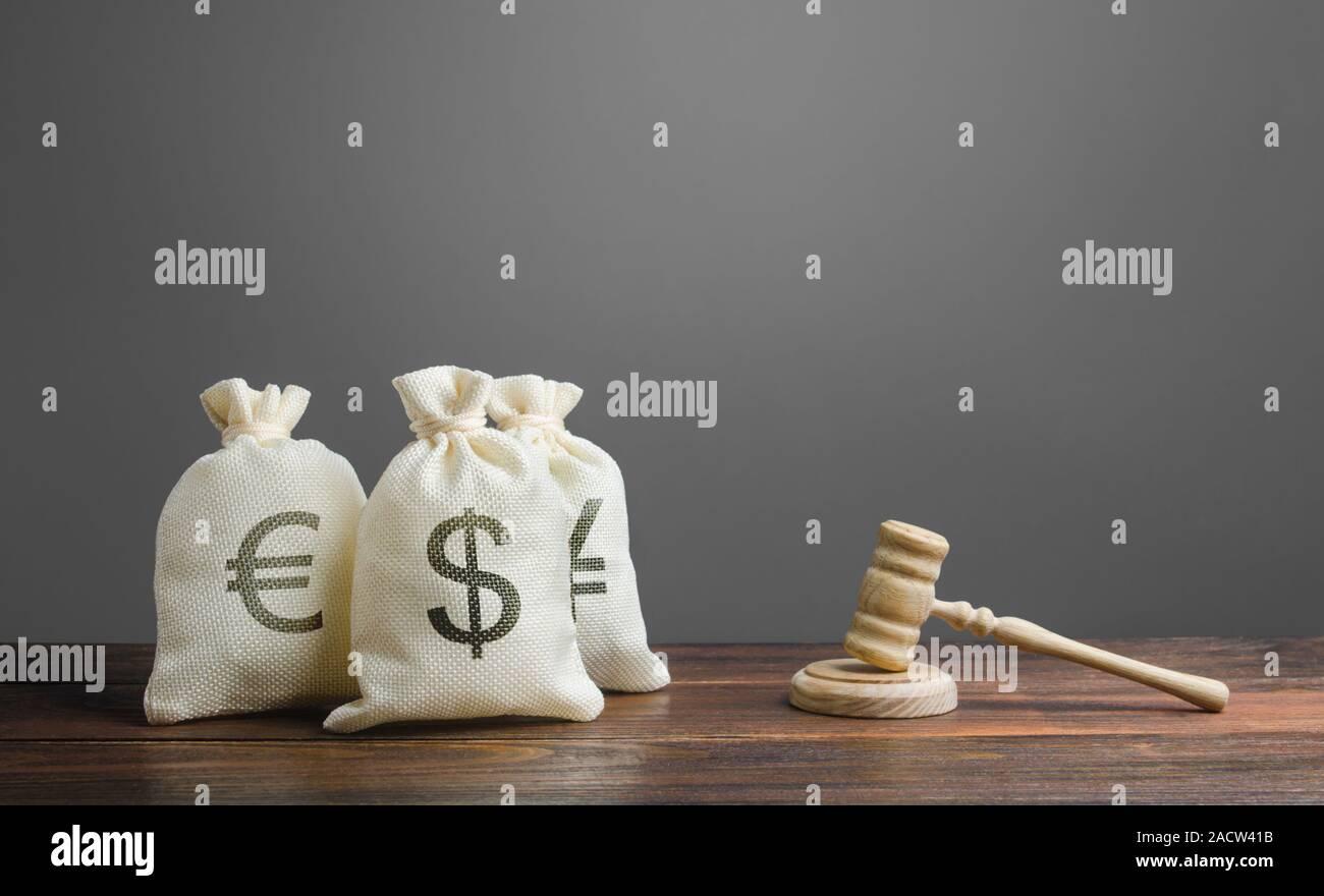 Beutel mit Geld und ein Richter Hammer. Gerichtsverfahren bei finanziellen Angelegenheiten. Rechtsvorschriften und Regeln, Gesetze im Finanzsektor der Wirtschaft. Investitionen und mov Stockfoto
