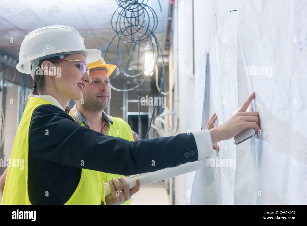 Erbauer und Bauarbeiter auf dem Gebäude blueprint Suche Stockfoto