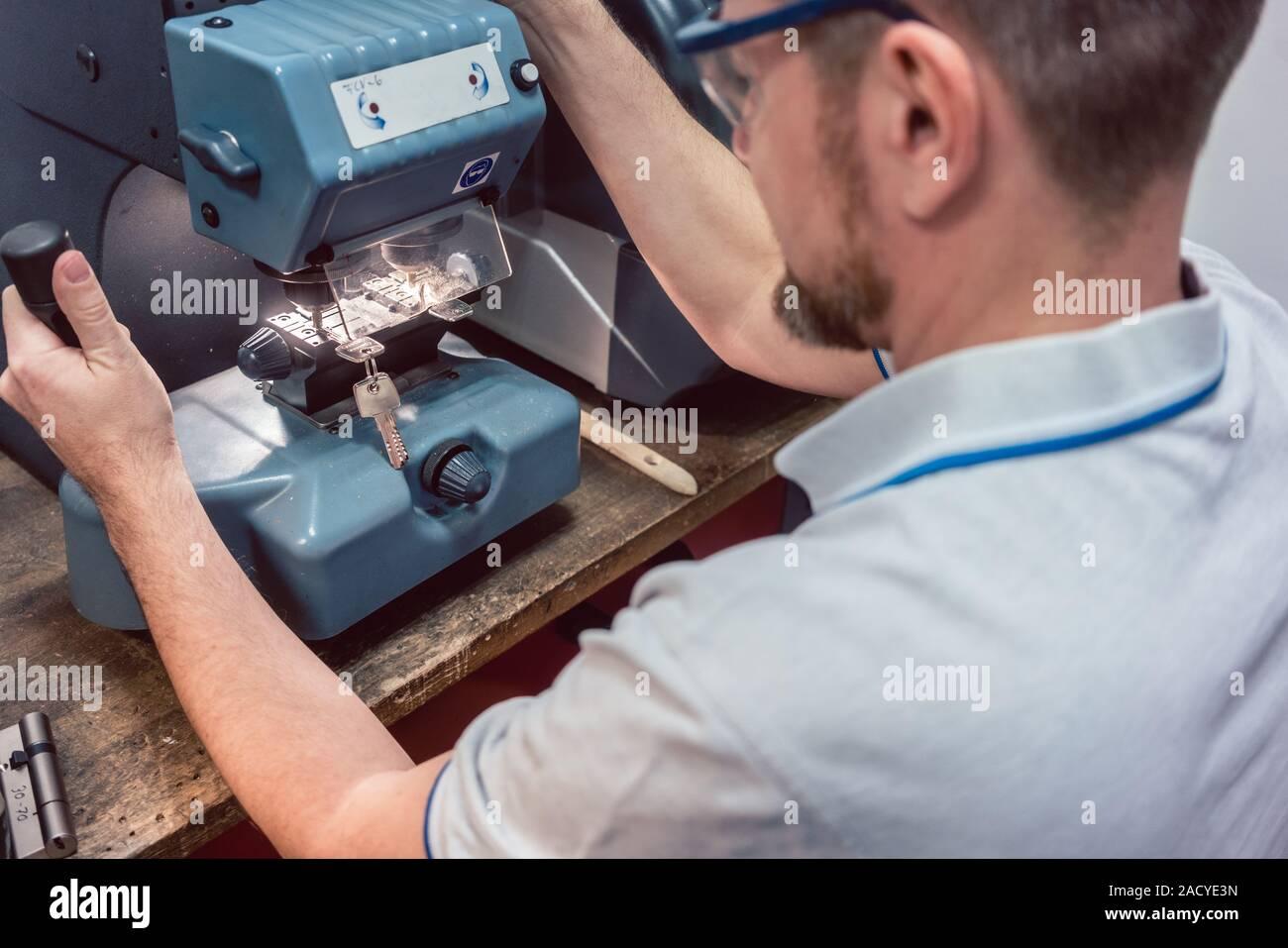 Schlosser schneiden Schlüssel mit seiner Maschine Stockfoto
