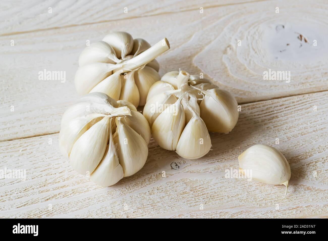 Drei Köpfe von rohem Knoblauch und eine Zehe auf einem weißen Holztisch. Würzig kochen Zutat. Vitamin gesunde Ernährung. Gemüse und Vegetarisch. Ansicht von oben. Stockfoto