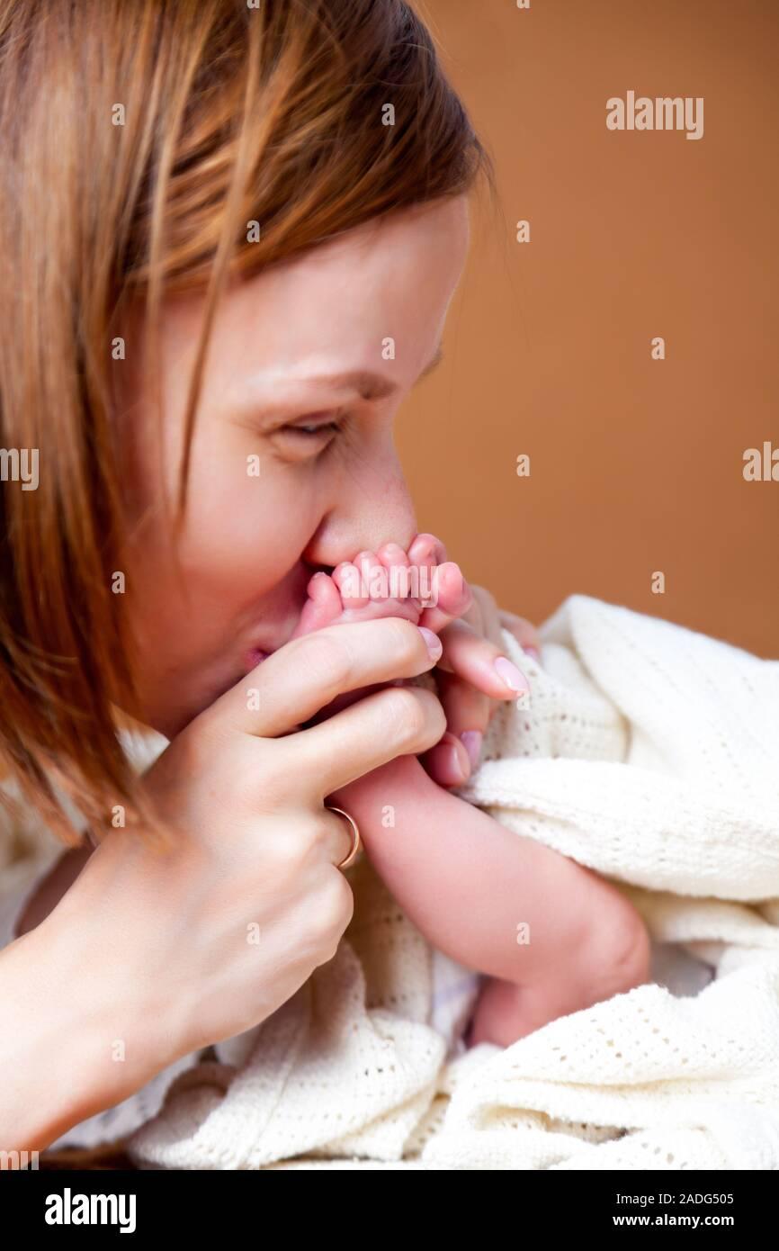 Home Portrait von Mutter, Hände halten und küssen ihr Kind, süßes neugeborenes Baby Rosa süße Füße in weißen Decke. Konzept lange erwarteten Sohn, IVF, Cesar Stockfoto