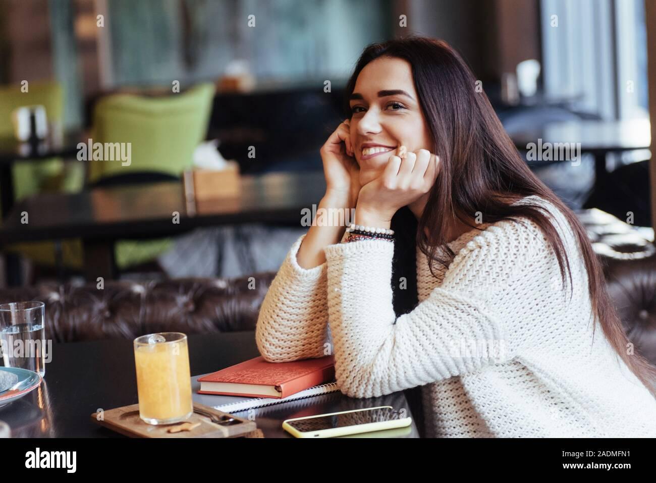 Schöne Frau. Fröhliche blonde Mädchen sitzen im Restaurant mit gelben Getränk auf den Tisch und lächelt Stockfoto
