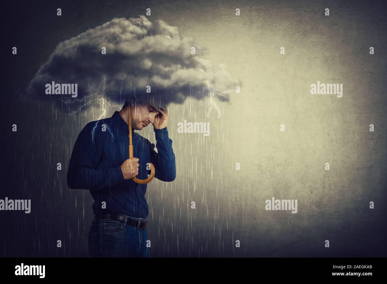Pessimistischer Mensch, stehen unter Regen, leiden Angst als Holding einen Regenschirm Gewitter wolke über dem Kopf. Konzept der Gedächtnisverlust und Demenz disea Stockfoto