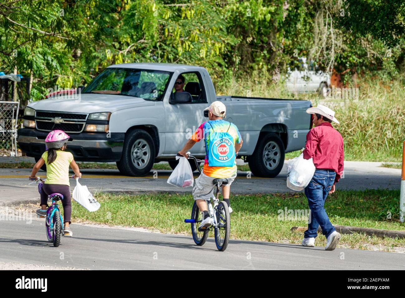 Florida Indiantown Hispanic Mann Mädchen Vater Tochter ländliche Stadt Familie Teen junge Mädchen Freunde Fahrrad Reiten Walking Pickup LKW Stockfoto