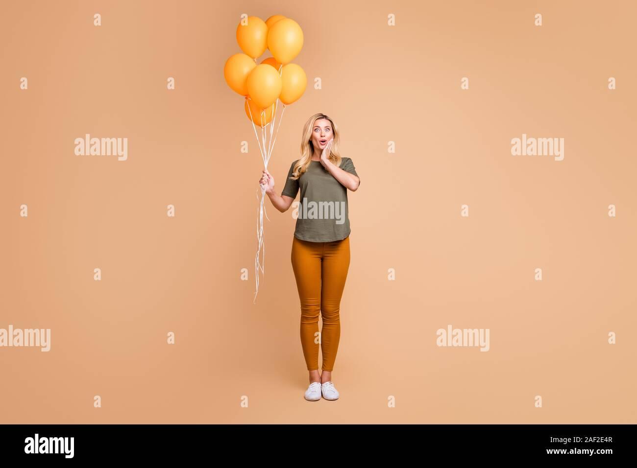 Voller Körper Foto von erstaunlich charmante blonde Dame emotionale Überraschung halten helle orange Luftballons kam Geburtstagsfeier tragen grüne t-shirt Hose Stockfoto