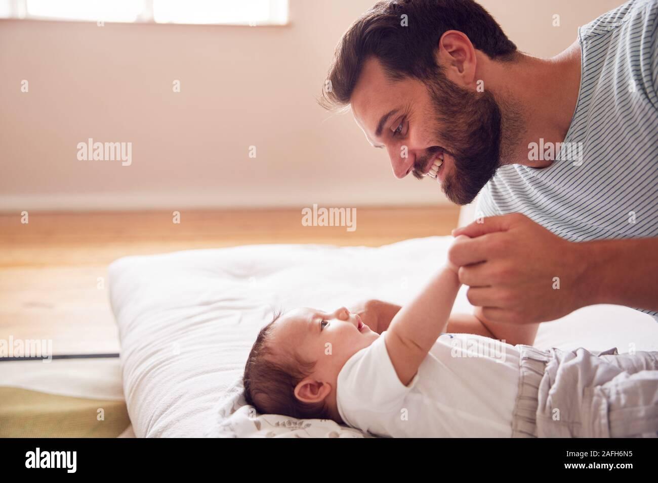 Liebevoller Vater Liegen mit neugeborenen Baby im Bett zu Hause in Loft Apartment Stockfoto