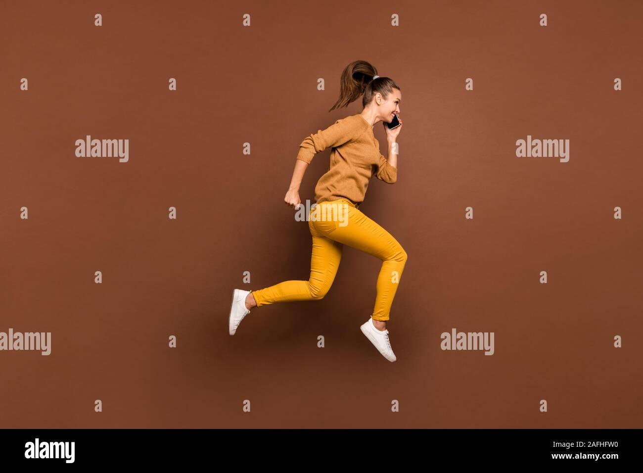 Volle Länge Körpergröße Seite Profil Foto von jungen Mädchen sprechen von ihrem Telefon in Richtung heruntergesetzte Shopping Mall laufen tragen Hosen Hosen isoliert Stockfoto