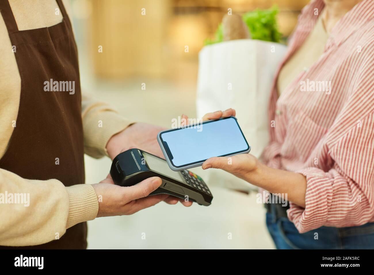 Nahaufnahme des unkenntlich moderne Frau Zahlung über NFC beim Einkaufen bei Farmers Market, Kopie Raum Stockfoto