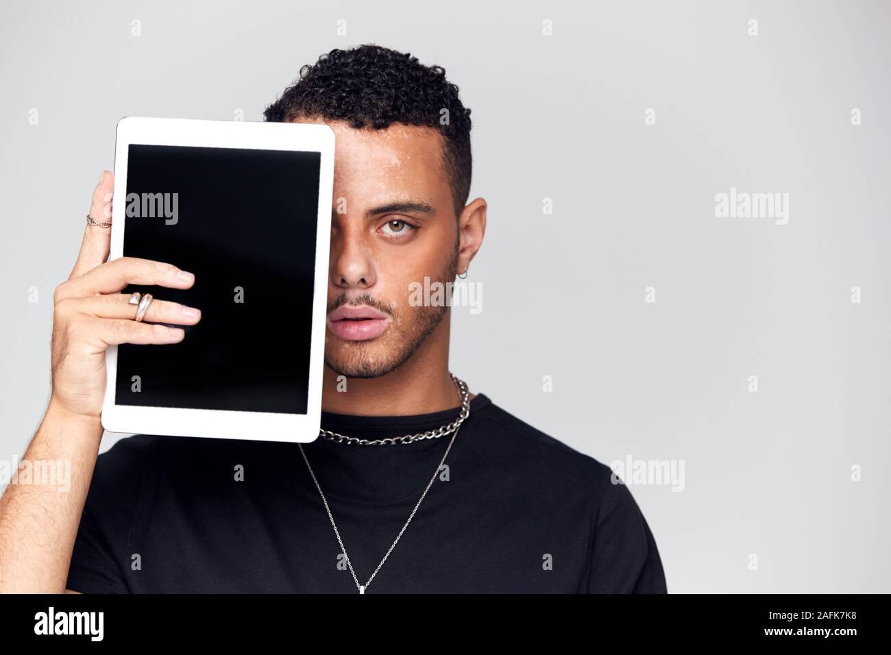 Studio Portrait von Sorgen junger Mann mit Gesicht mit digitalen Tablet Stockfoto
