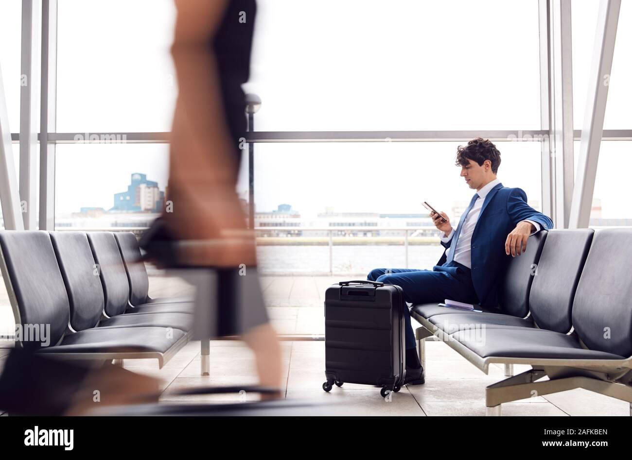 Unternehmer Sitzen In hektischen Airport Departure Lounge mit Handy Stockfoto