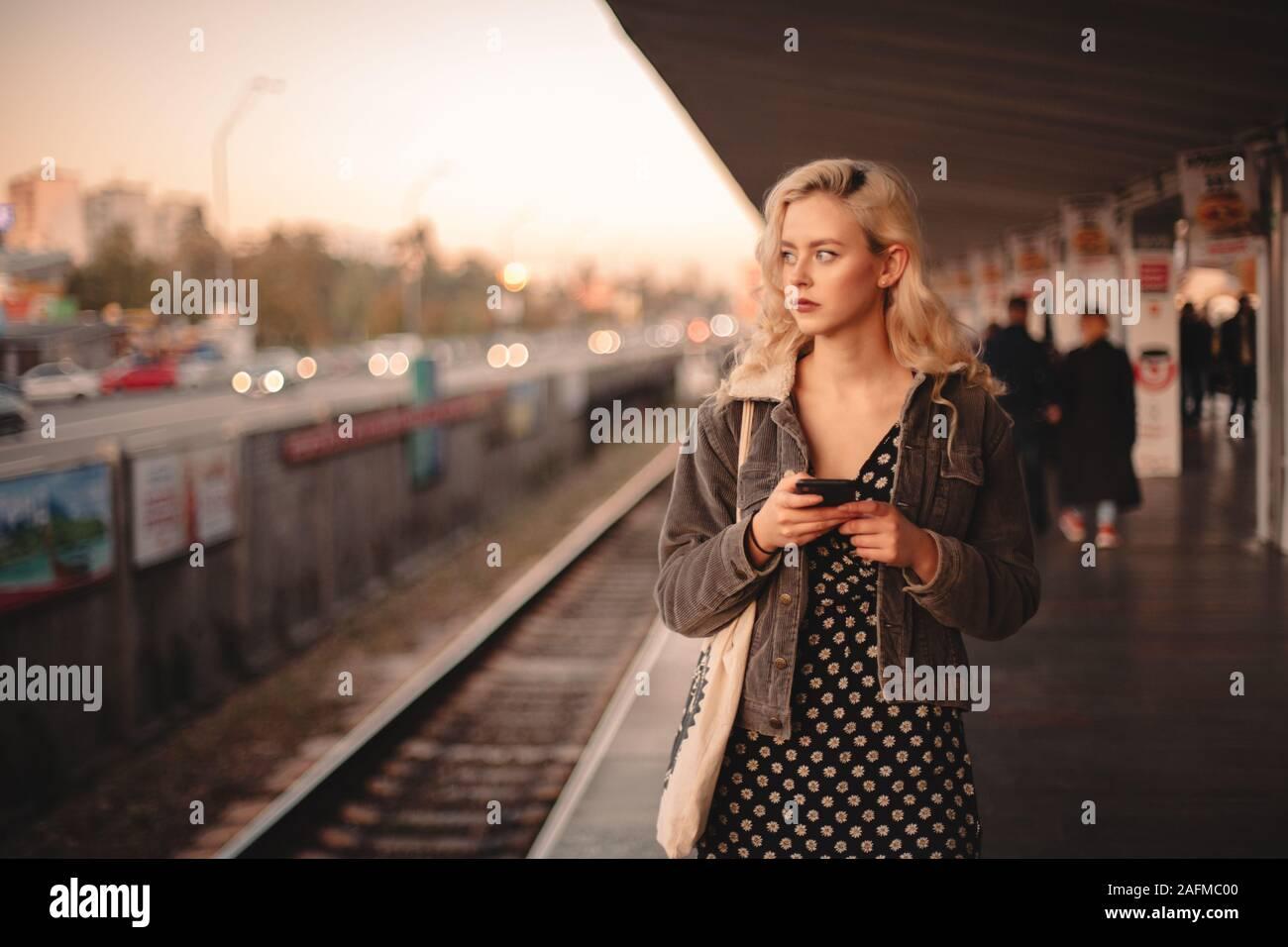 Junge nachdenkliche Frau mit Smart Phone beim Warten auf die Bahn Stockfoto