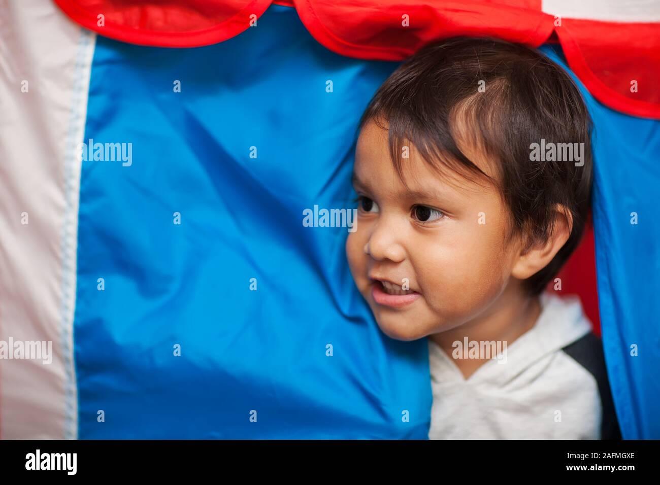 Das Gesicht der ein kleines Kind mit Wuscheligen Haaren, dazwischen der Eingang zu einem Spiel Zelt, die roten, weißen und blauen Farbtönen. Stockfoto