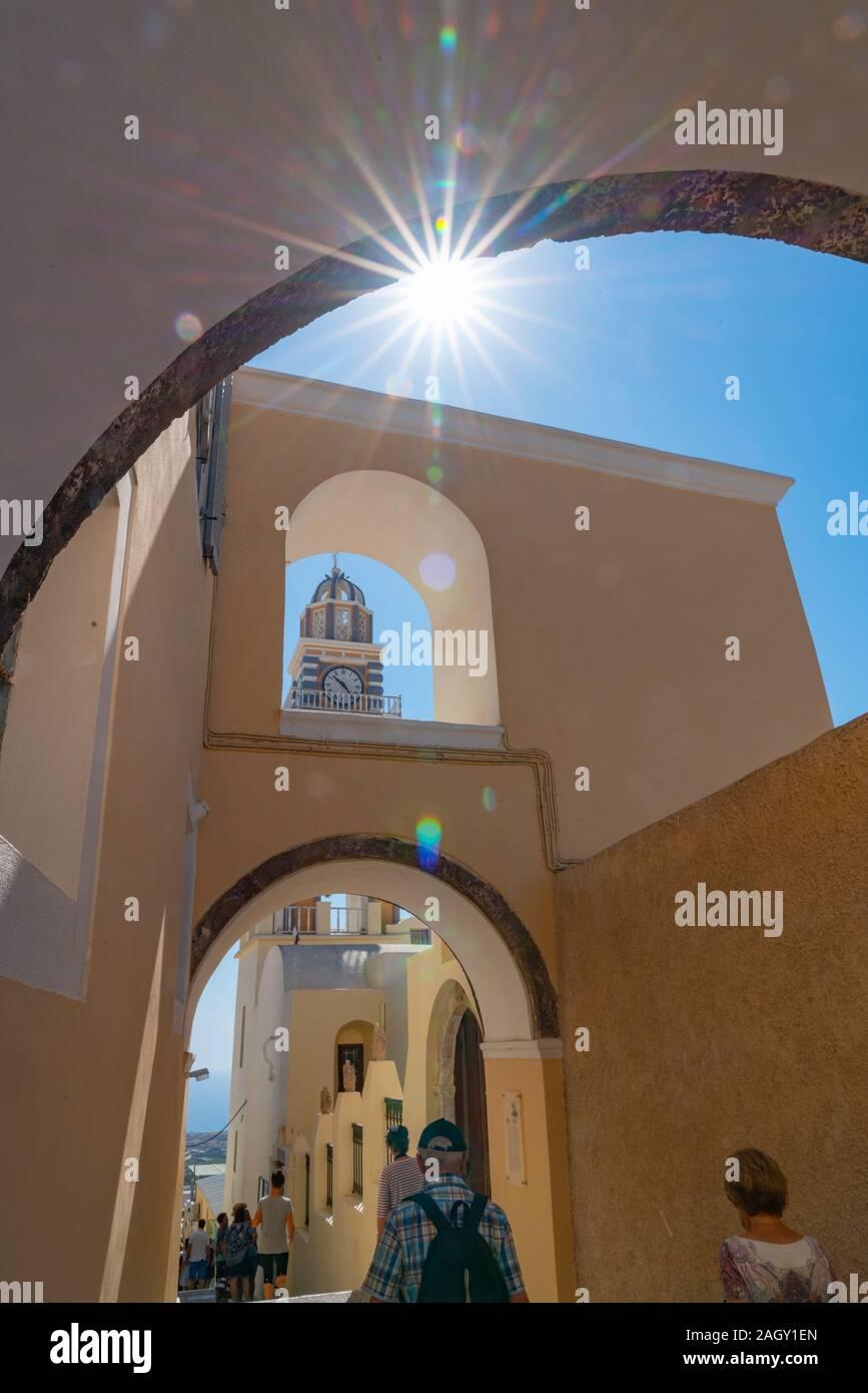 Santorini Griechenland - 8. August 2019; Sun blasts durch unter einem Bogen im Line up der architektonischen Merkmale der Bögen, Glockenturm und Uhr in Fira, der als Stockfoto