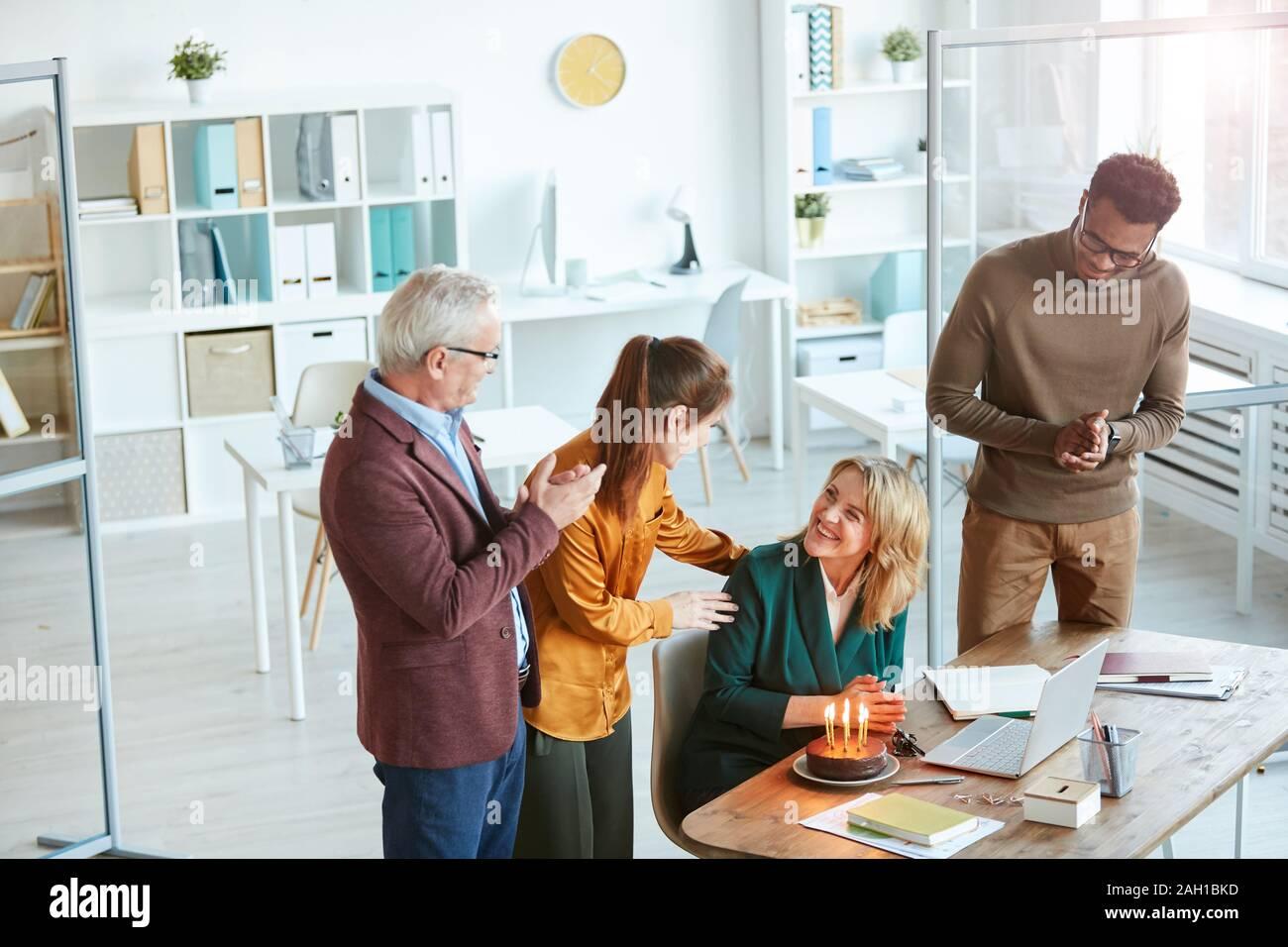 Gruppe von Geschäftsleuten gratulieren Sie Ihren Kollegen mit Geburtstag Kuchen mit Kerzen Stockfoto