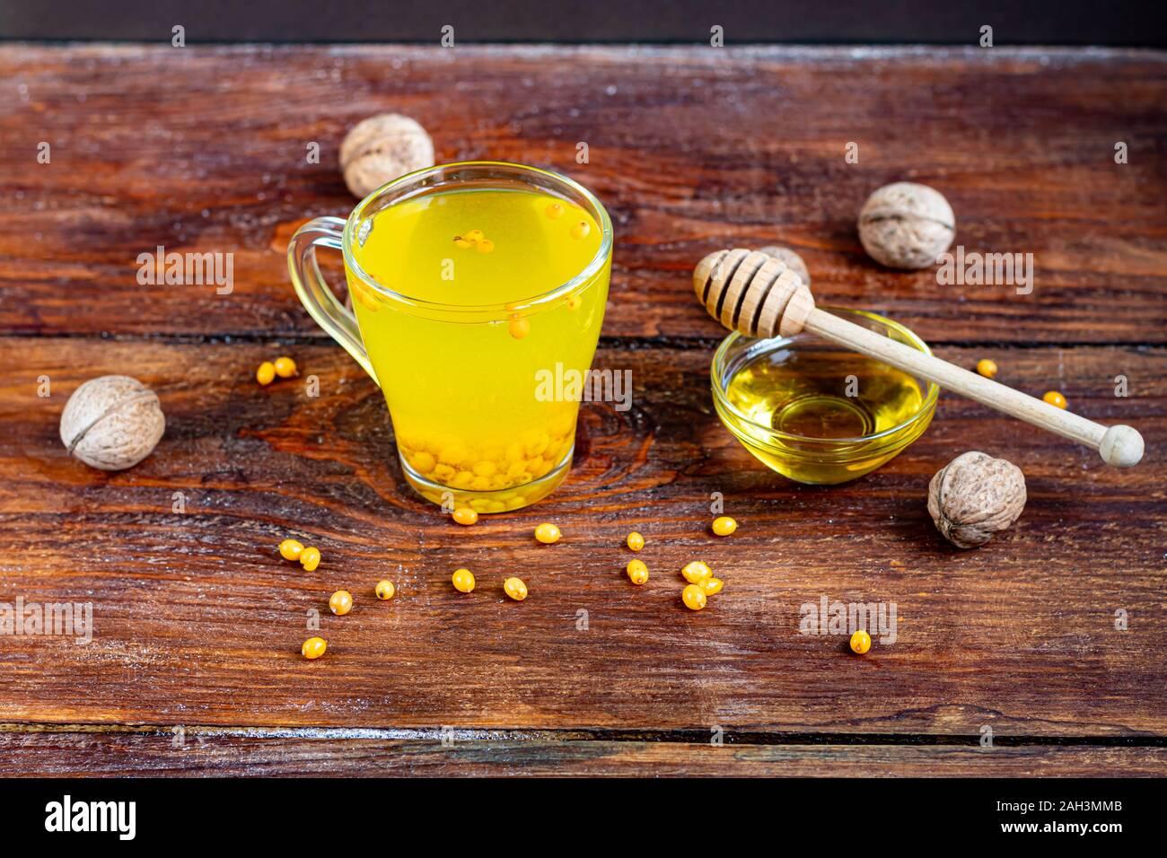 Ein wärmendes Getränk. Sanddorn Tee. Trinken Sie mehr oft im Herbst oder im Winter. Gut für die Gesundheit. Eine Menge Vitamine und Mineralien. Auf einer hölzernen backgr Stockfoto