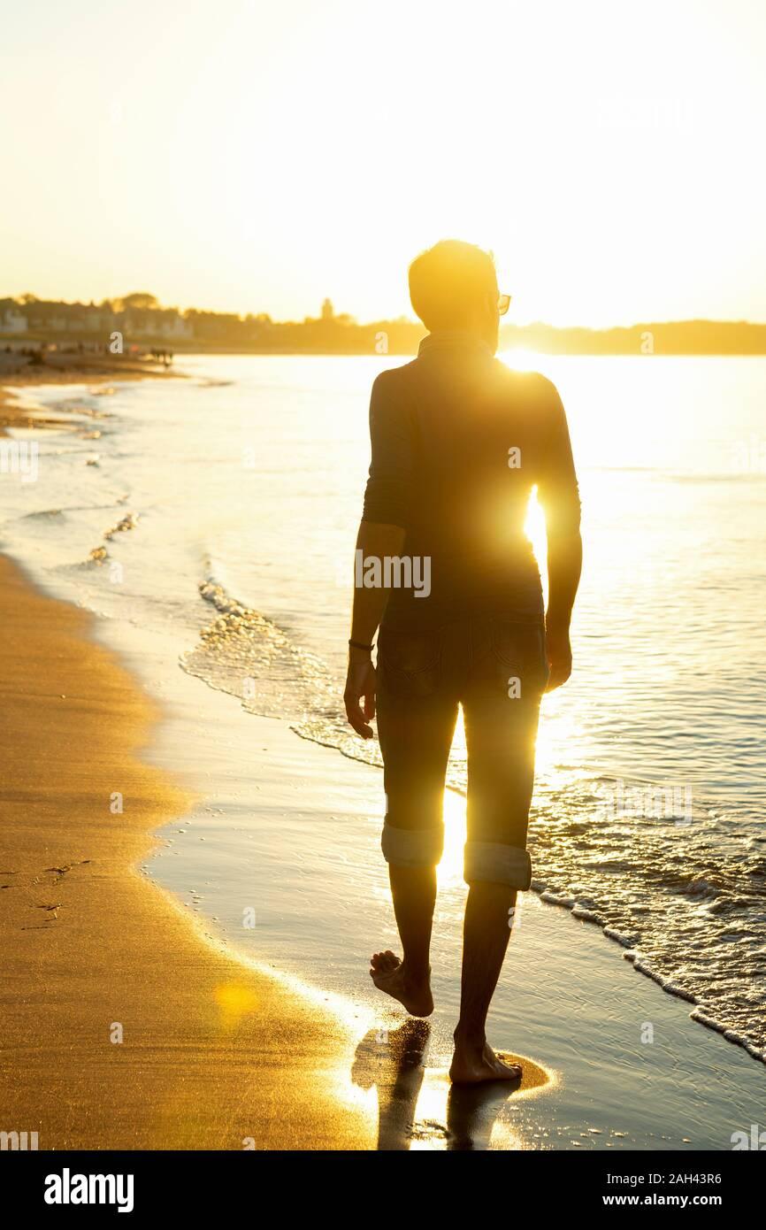 Man Walking am Strand bei Sonnenuntergang, Warnemünde, Deutschland Stockfoto