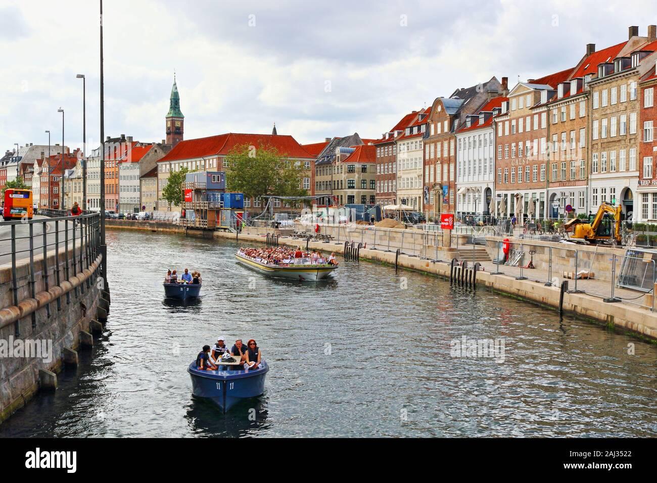 Sightseeing Tour Boote auf einem Kanal und Slotsholmen Gammel Strand Straße durch eine Reihe von bunten alten Häusern im Zentrum von Kopenhagen, Dänemark gefüttert Stockfoto