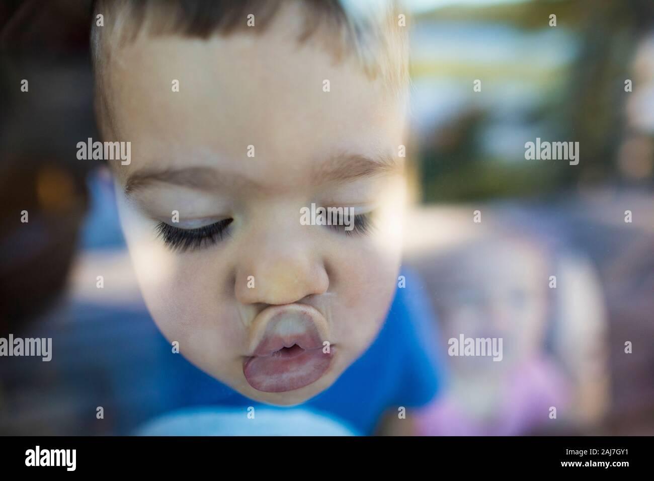 Der junge Junge schiebt seine Lippen gegen ein Fenster, um einen Kuss zu machen Stockfoto