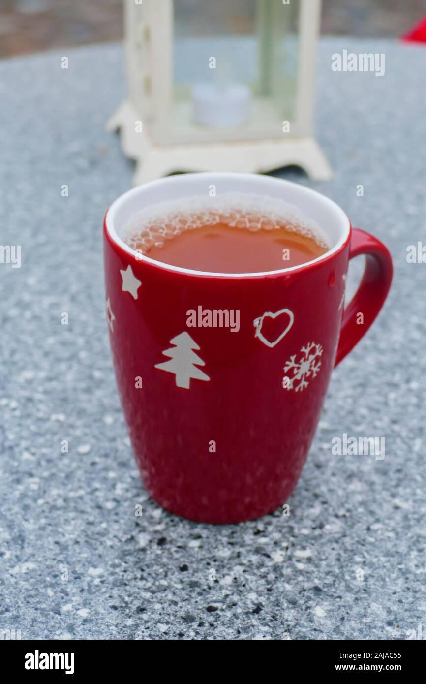 Rote Weihnachts- Tasse mit Glühwein steht auf einem Tisch Stockfoto
