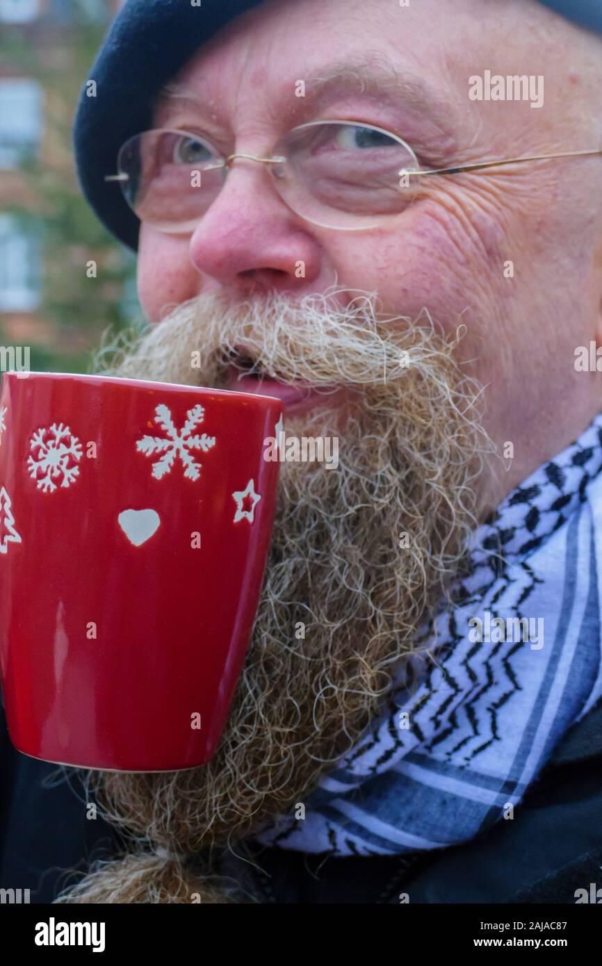 Mann mit langem Bart und Brille, trinkt eine Tasse Glühwein Stockfoto