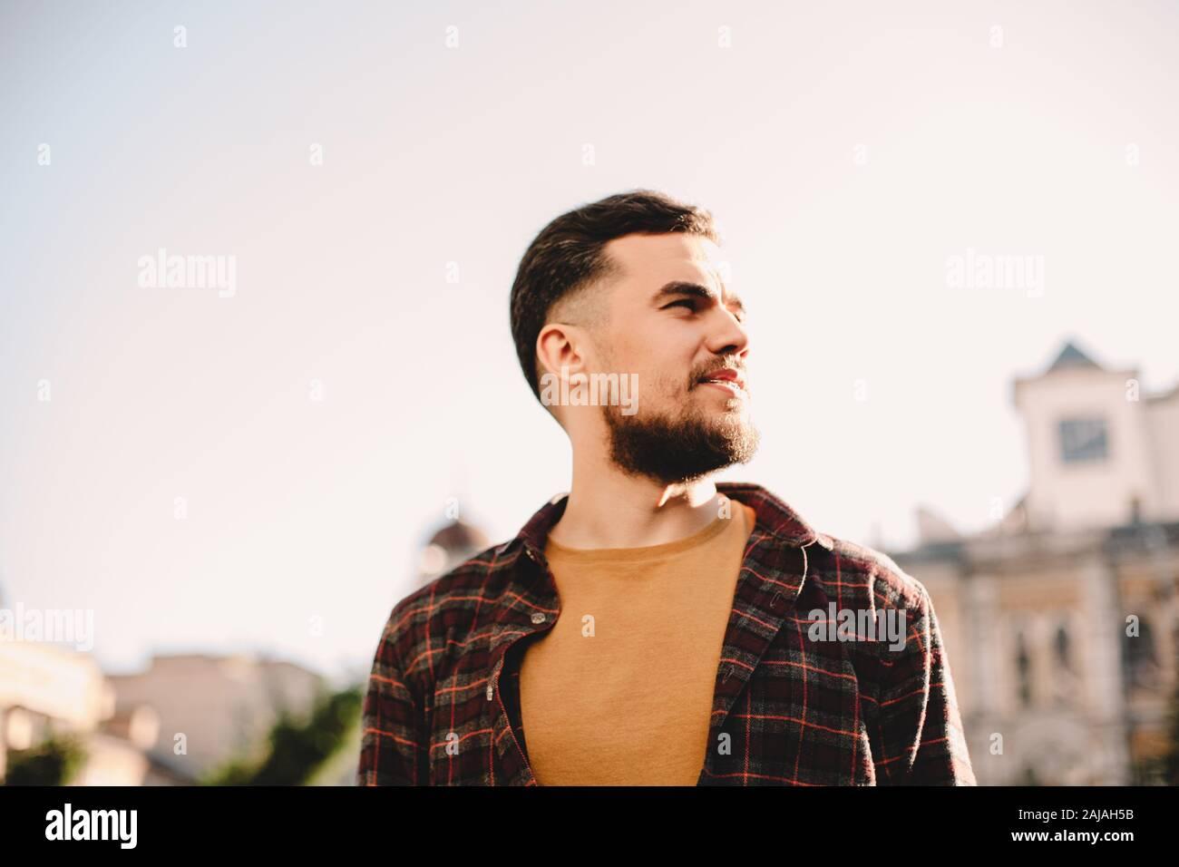 Porträt des selbstbewussten jungen Hipster Mann gegen klaren Himmel in der Stadt Stockfoto