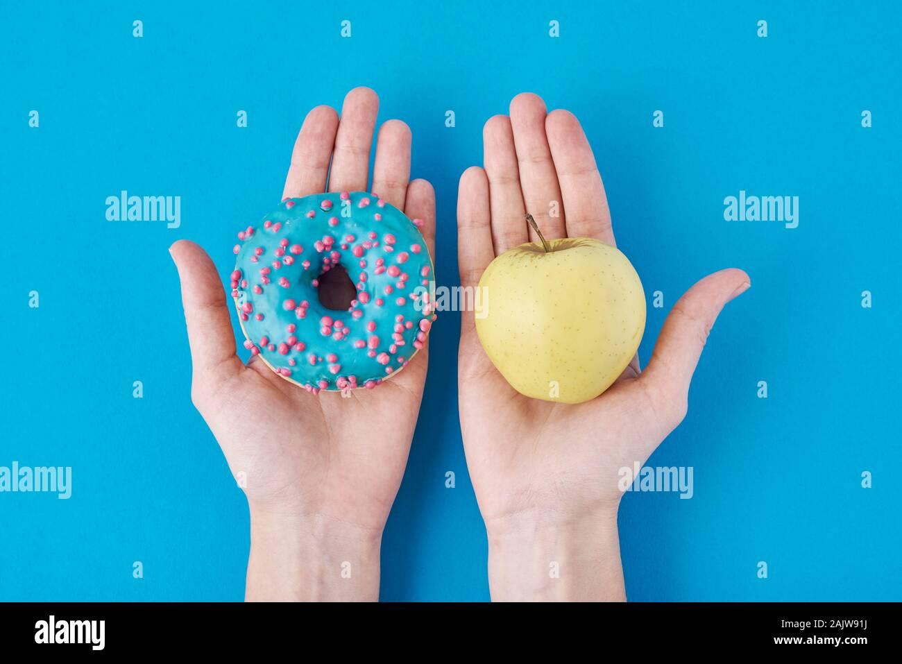 Frau zwischen Apple und Krapfen, die beschließen, in ihre Hände. Gesunde Ernährung Konzept Stockfoto
