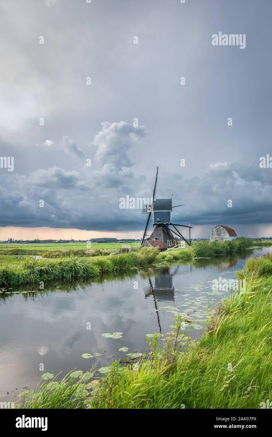 Gewitter über eine klassische holländische Landschaft mit Canal und Windmühle Stockfoto