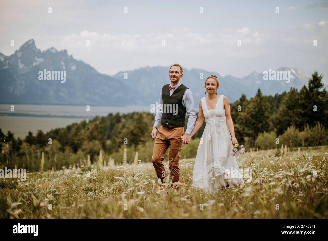Braut und Bräutigam spazieren durch Wildblumen vor den Teton Bergen Stockfoto