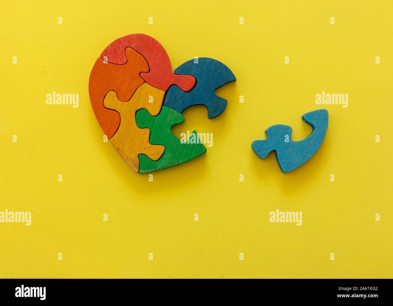 Holz- Cognac Puzzle in Form von Herzen auf gelben Hintergrund. Konzept Valentines Tag, Beziehung. Stockfoto