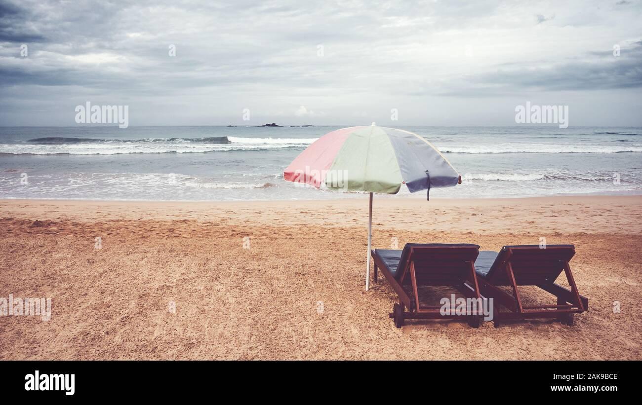 Zwei Sonnenliegen und Sonnenschirm auf einen leeren Strand, Farbe Tonen angewendet, Sri Lanka. Stockfoto