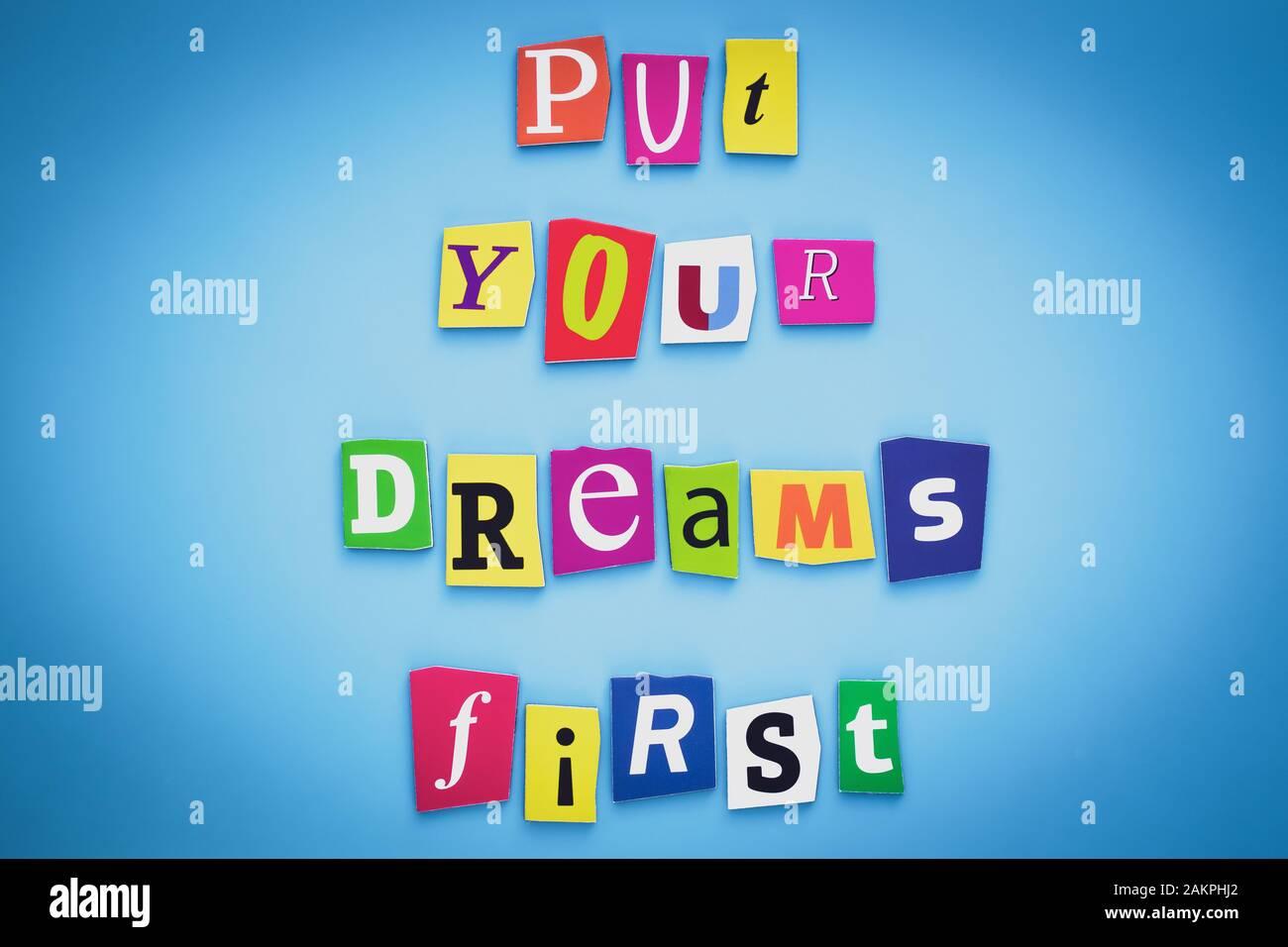 Setzen Sie Ihre Träume an die erste Stelle. Positives Denkkonzept. Text aus geschnittenen bunten Buchstaben auf blauem Hintergrund. Schreiben auf Banner, Karte. Beschriftung, Nachricht auf po Stockfoto