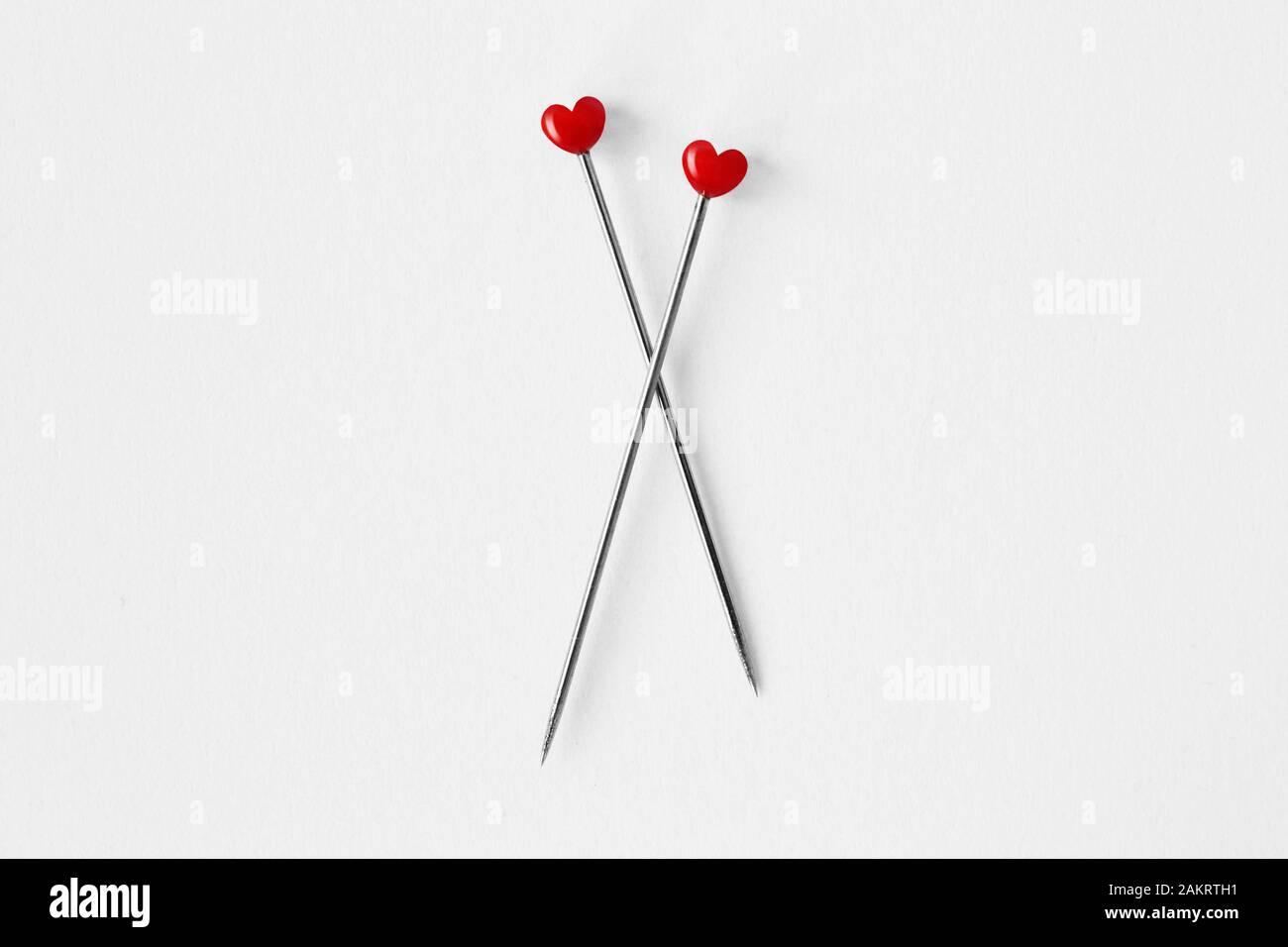Zwei herzförmige Stifte auf weißem Hintergrund - Konzept von Liebe und Beziehung Stockfoto