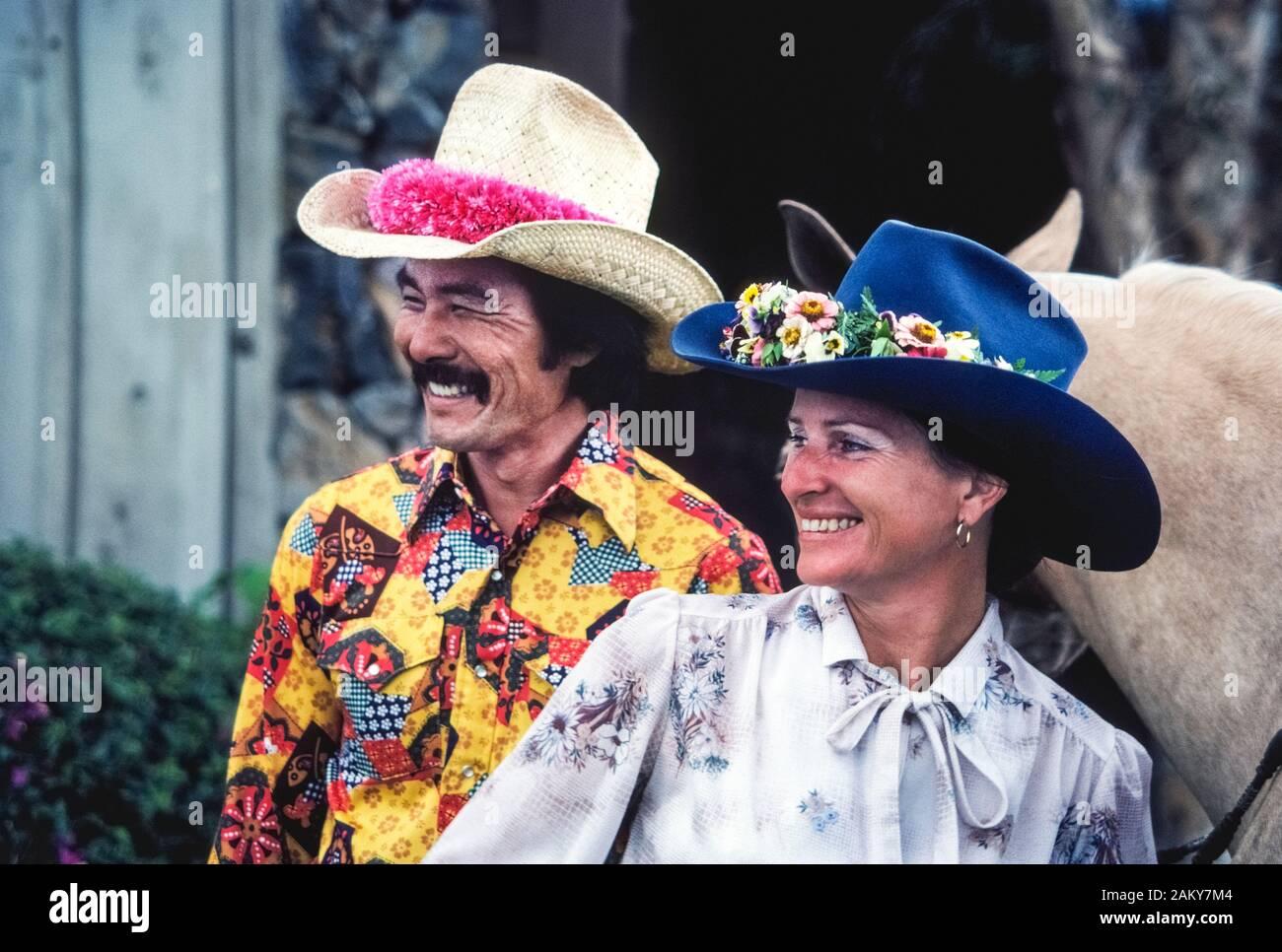 Trägt ein schickes Hemd und eine rosa Blume lei Um seinem Strohhut, eine hawaiische Paniolo (Cowboy) und seine Freundin verkleiden sich die jährlichen 4. Juli Rodeo am historischen Parker Ranch auf der grossen Insel von Hawaii in Hawaii, USA zu besuchen. Gebürtige Hawaiianer wurde Cowboys vor langer Zeit, im Jahre 1847, wenn die Rinder Ranch war auf dem Pazifischen Ozean Insel gegründet und wuchs zu einem der größten privaten Ranches in den Vereinigten Staaten zu werden. Heute ungefähr 17.000 Angus, Charolais Rind rinder weiden auf den Wiesen der Parker Ranch, die 130.000 Hektar im Zentrum der Großen Insel. Stockfoto