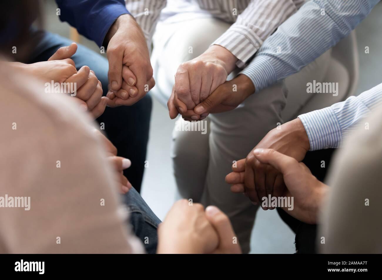 Menschen, die im Kreis sitzen und die Hände während der Gruppentherapiesitzung halten Stockfoto