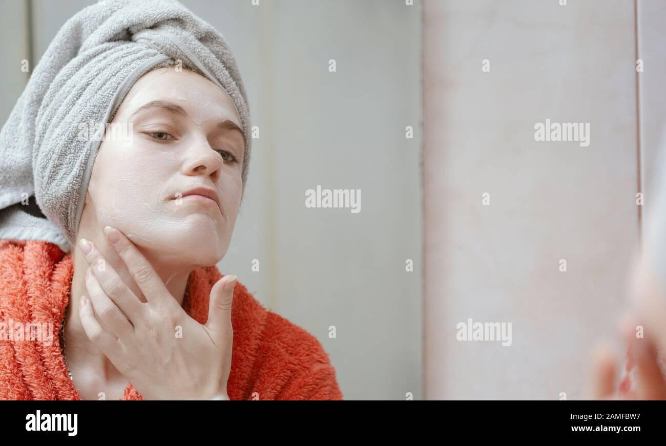 Schönes junges glückliches Mädchen, das ihr Gesicht mit hausgemachter Kosmetikmaske verschmiert und in den Spiegel schaut. Haut- und Gesundheitspflege, umweltverträglichkeit Naturprodukte Konzept. P Stockfoto