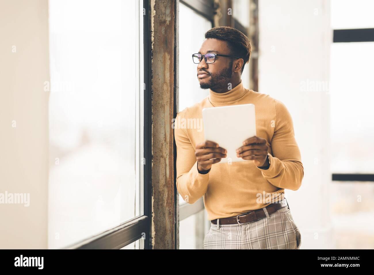 Träumender Afro Manager mit wegschauendem Tablet Stockfoto