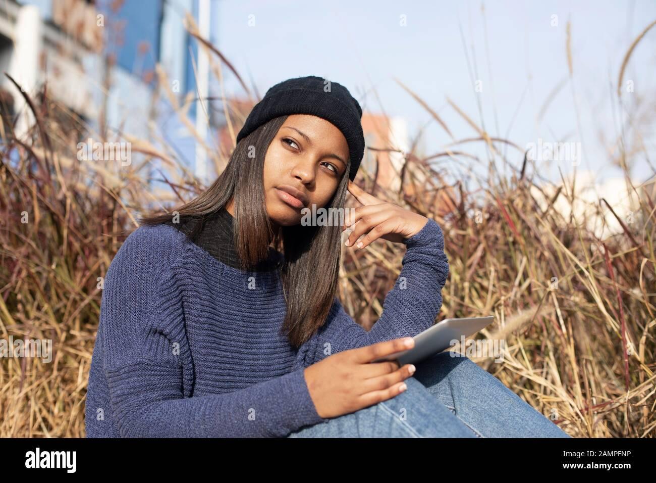 Porträt der jungen afroamerikanischen Frau, die eine Wollkappe trägt, die auf der Straße steht, während sie ein Mobiltelefon verwendet Stockfoto
