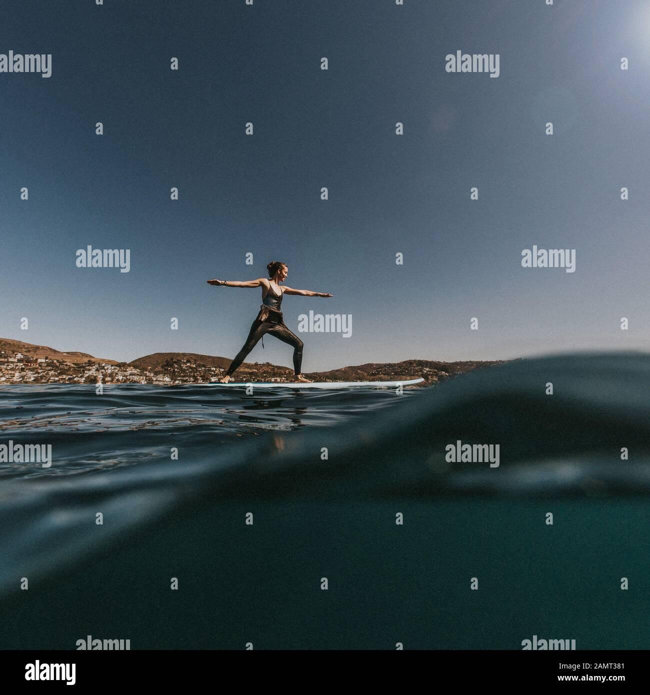 Frau, die zwei Positionen auf einem Paddleboard, Laguna Beach, Kalifornien, USA, macht Stockfoto