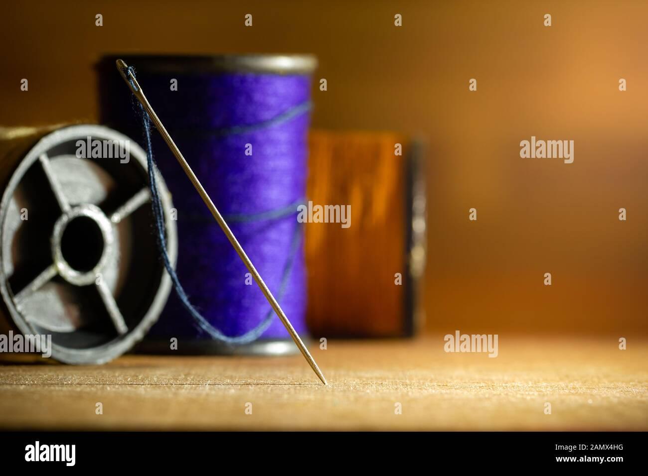 Nadel und Threads auf Holztisch. Closeup kopieren und Platz für Text. Konzept der maßgeschneiderten oder Designer. Stockfoto