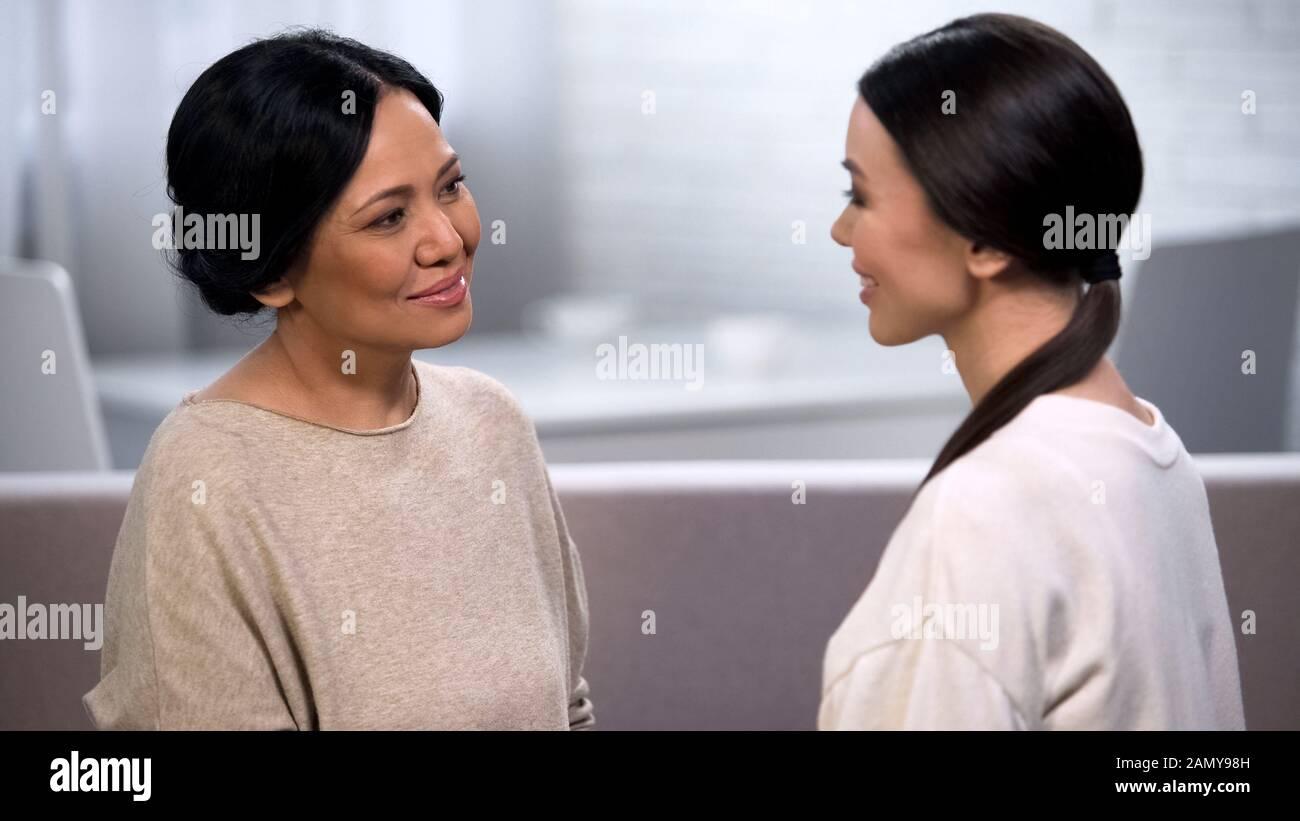 Mutter spricht mit Tochter, zärtlich betrachtet sie, gibt Ratschläge, Mutterschaft Stockfoto