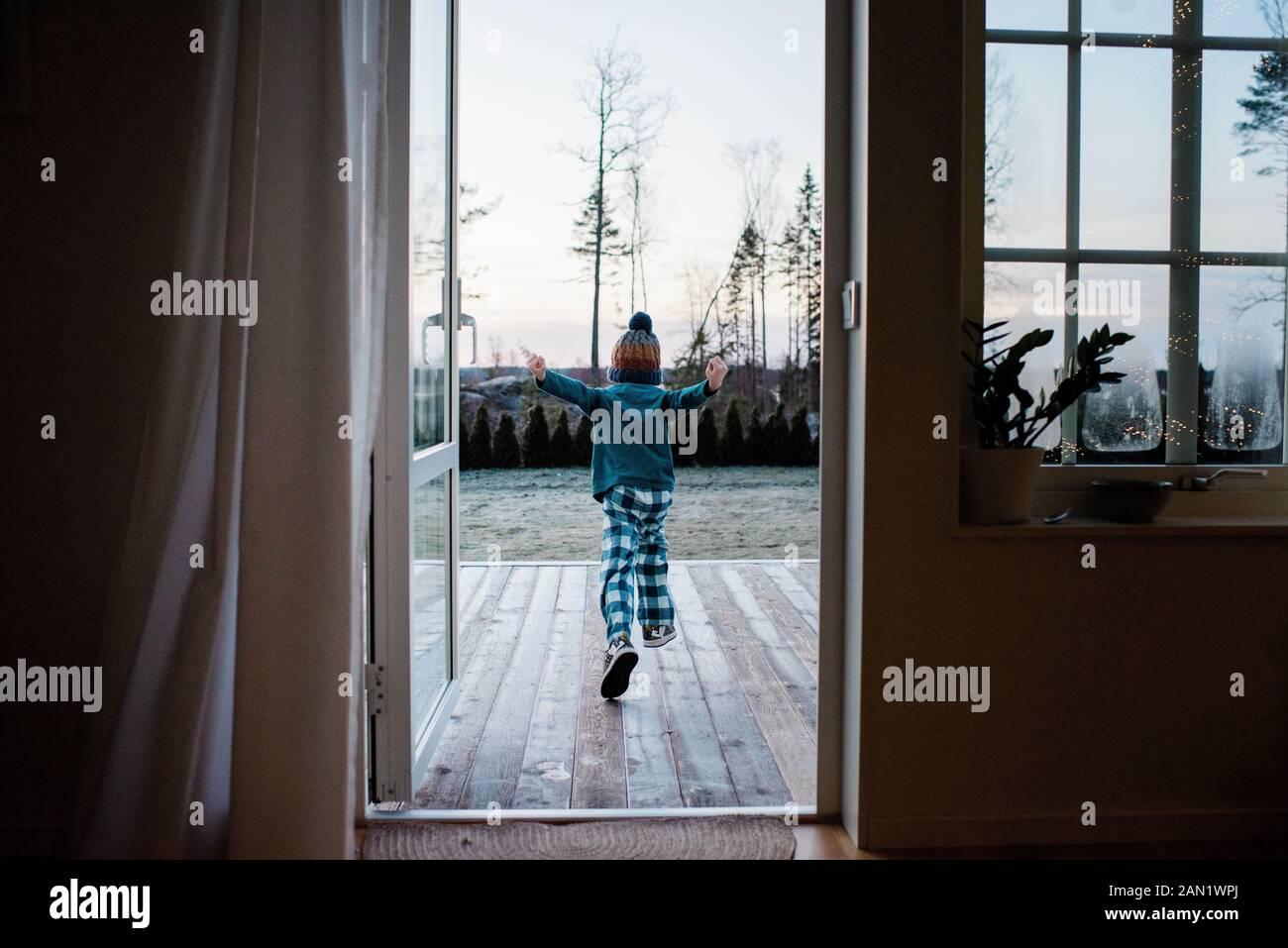 Kleiner Junge läuft aus der Hintertür, um draußen im Winter zu spielen Stockfoto