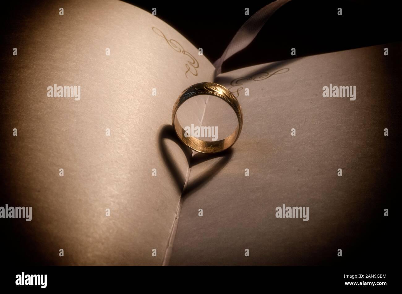Gold Hochzeit Ring Schatten macht valentine Herzen, auf einem alten Buch, warmes Licht gegossen goldenen Ring Schatten. valentinstag - Ring Schatten Stockfoto