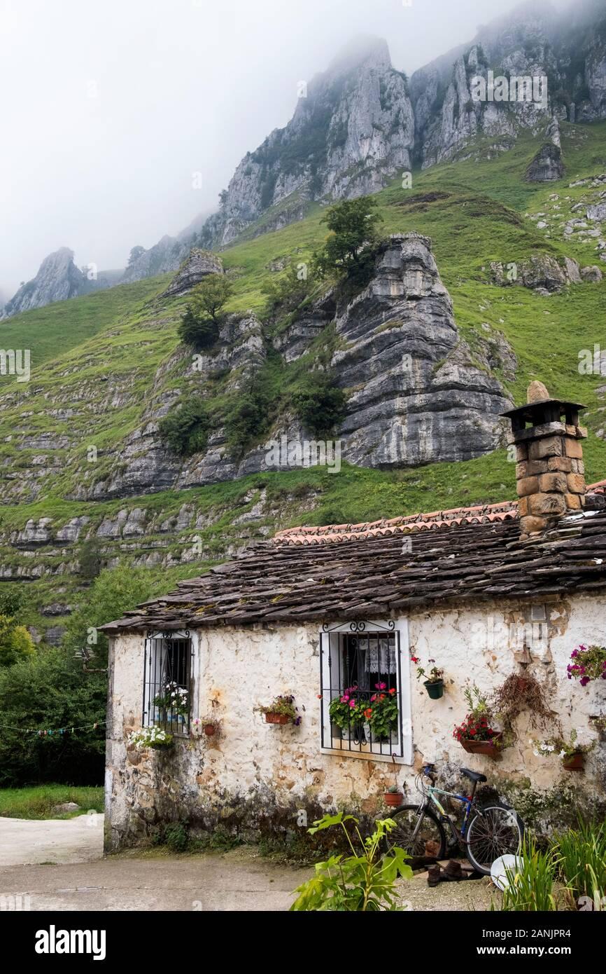 Traditionelles Steinhaus am Fuße der Kalksteinauswüchse im Tal Valle del Miera (San Roque de Riomiera, Valles Pasiegos, Kantabrien, Spanien) Stockfoto