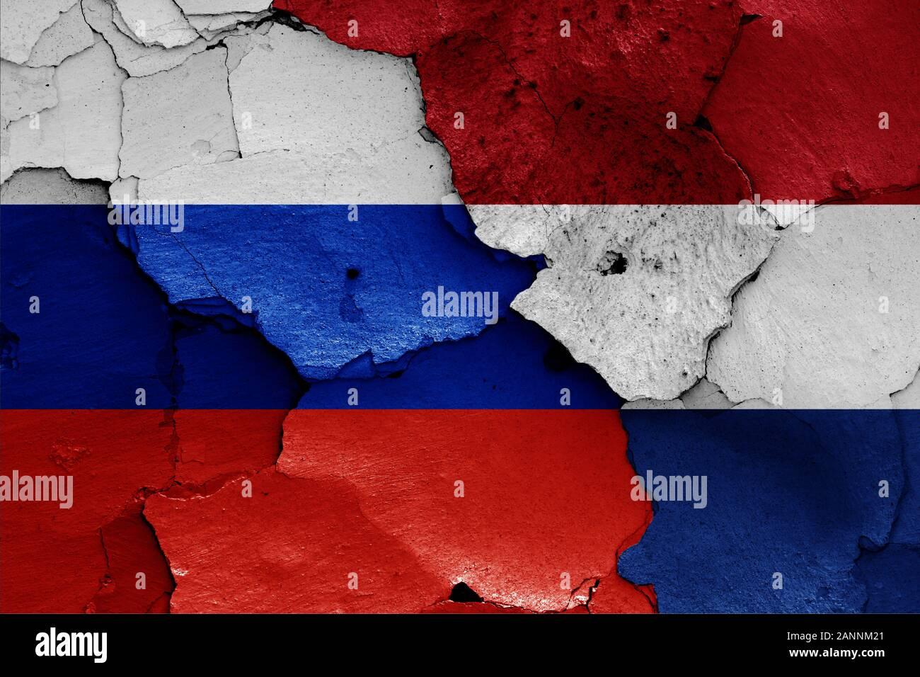 Flagge von Russland und die Niederlande Malte auf Risse an der Wand Stockfoto