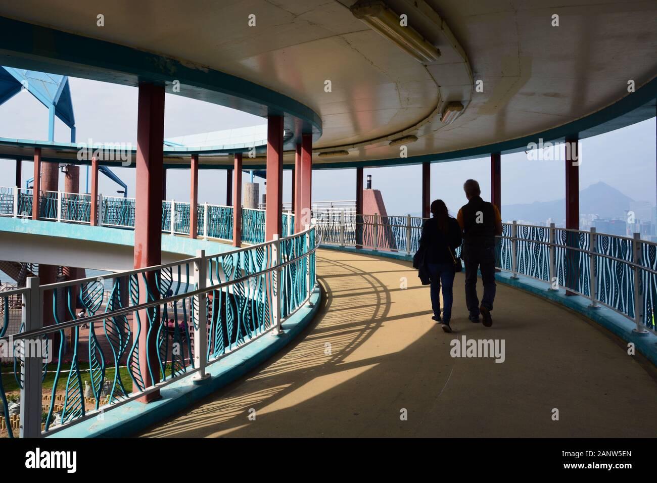 Die Fußgängerüberführung im Quarry Bay Park entlang des Victoria Harbour in Hongkong. Stockfoto