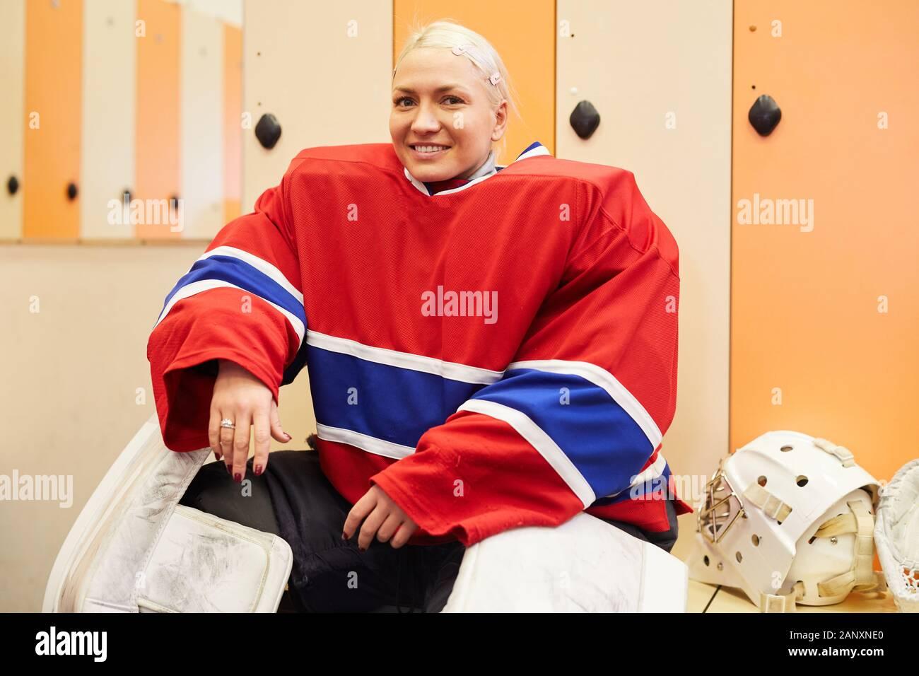 Porträt der jungen weiblichen hockey player lächelnd in die Kamera während im Schließfachraum posiert vor dem Match, kopieren Raum Stockfoto