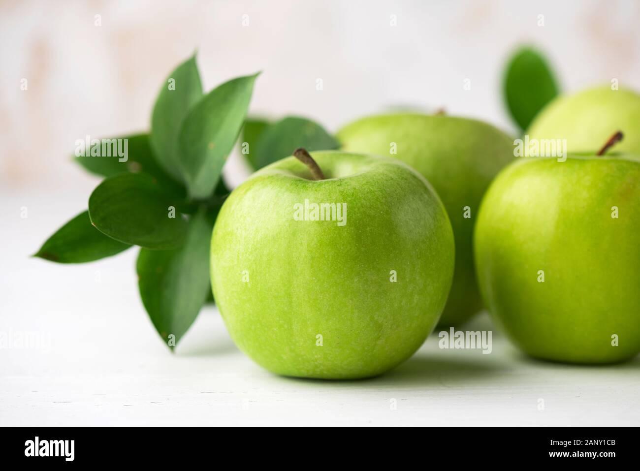 Grüne Äpfel mit grünen Blättern auf weißen Tisch Detailansicht. Gesunde knackig frische Früchte Stockfoto