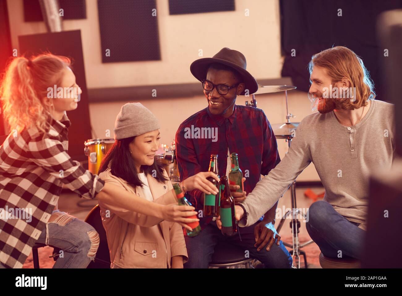 Multi-ethnischen Gruppe junger Leute Bier trinken, während Sie die Probe im Music Studio Stockfoto