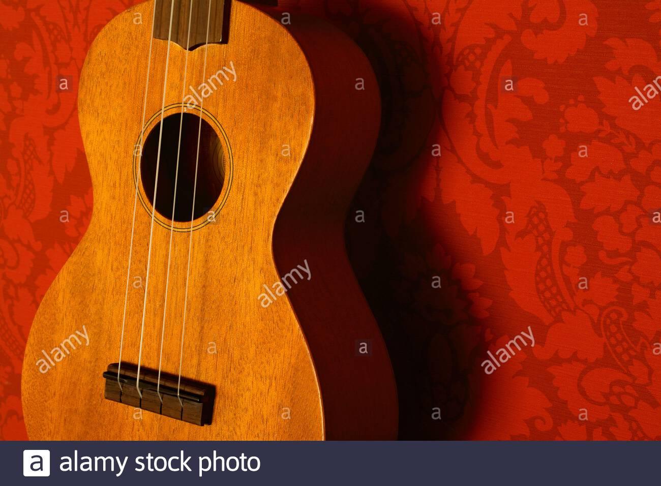 Nahaufnahme einer Ukulele mit honigfarbenem Holz vor rotem Tapetenhintergrund Stockfoto