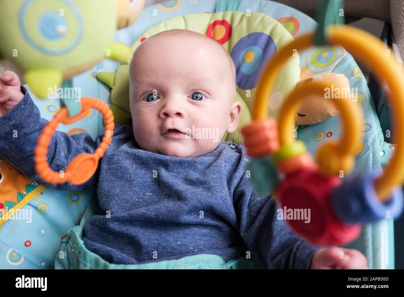 Authentisches Bild eines süßen Jungen im Alter von fünf Monaten in einem Aktivitätsstuhl, der Interesse an interessanten hängenden Spielzeugen hat. England, Großbritannien, Großbritannien Stockfoto